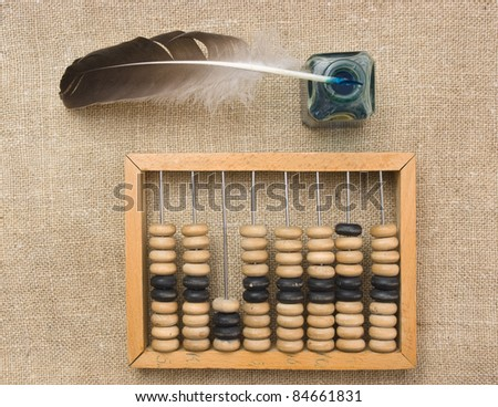old glass inkwell with a quill pen and abacus on a wooden table