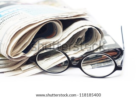 Old glasses and newspaper on white background