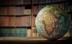 Old globe on bookshelf background. Selective focus. Retro style. Science, education, travel, vintage background. History team.
