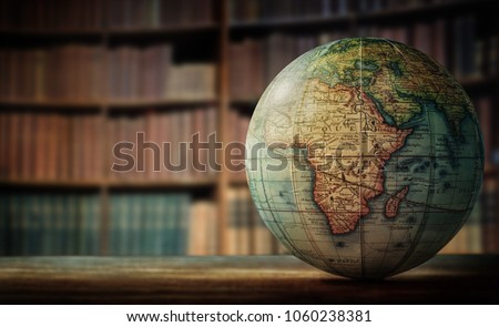 Old globe on bookshelf background. Selective focus. Retro style. Science, education, travel, vintage background. History team.