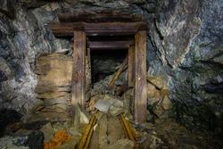 Old gold mine underground tunnel with wooden door