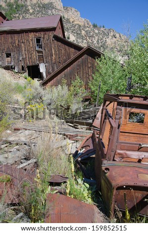 Old gold mining structure and rusted antique car at Bayhorse, Idaho ghost town.