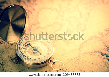 Old  gold vintage compass on vintage map:Heading south