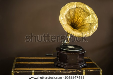 Old golden gramophone with horn speaker stands against anicent background, produces songs recorded on plate. Music and nostalgia concept. Gramophone with phonograph record #1065547685