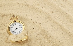 Old golden watch buried in sand