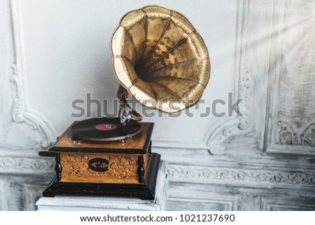 Old gramophone with horn speaker stands against anicent background, produces songs recorded on plate. Music and nostalgia concept. Gramophone with phonograph record #1021237690