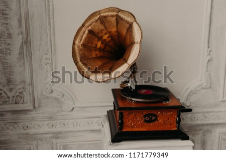 Old gramophone with horn speaker stands against anicent background, produces songs recorded on plate. Music and nostalgia concept. Gramophone with phonograph record #1171779349