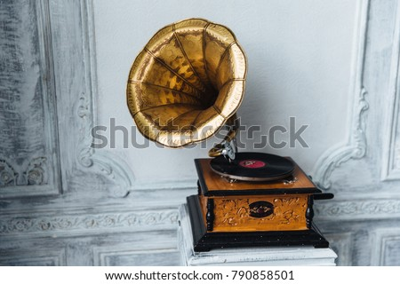 Old gramophone with horn speaker stands against anicent background, produces songs recorded on plate. Music and nostalgia concept. Gramophone with phonograph record #790858501