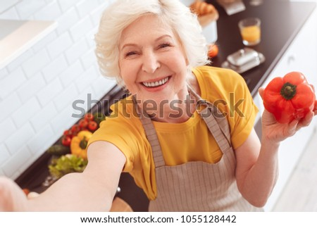 Old grandma making selfie toothy smile, holding a red pepper