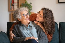 Old grandmother and adult granddaughter hugging at home and looking at each other. Happy senior mother and young daughter embracing with love on sofa. Happy woman hugging from behind grandma with love
