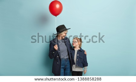 Old grandmother and small child have nice conversation, hold red air balloon, express love to each other, isolated over blue background. Granddaughter celebrates birthday with caring granny.
