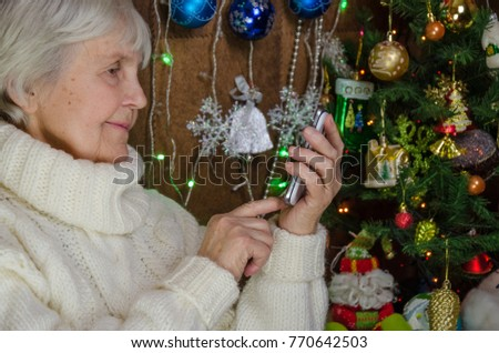 old grandmother in new year took up phone. senior lady enjoy smartphone in her adult hand. granny in white knitted sweater answers call. elderly woman near christmas tree. finger touches touch screen #770642503