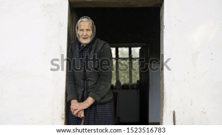 Old grandmother on a background of an old house