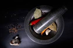 Old granite mortar with pestle with spices ready for grinding, isolated on black background.