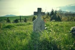 Old grave on traditional European cemetery in Slovakia. Aged cross tomb stone on grave yard in spring