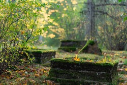 old grave places with green moss on the borders in country cemetery