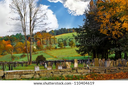 Old graveyard in the countryside during autumn with colorful leaves and trees.  Dramatic clouds and sun rays overhead. - stock photo