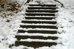 Old gray concrete steps on the hill covered with white snow, drifts with fallen yellow leaves. The first snow in the autumn, in October. Autumn and winter background