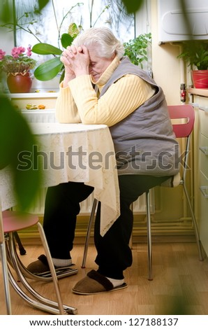 old gray-haired woman sitting in the kitchen