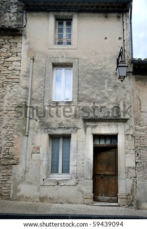 Old gray house facade with wooden door