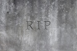 Old gray stone headstone with text R.I.P. carved in it