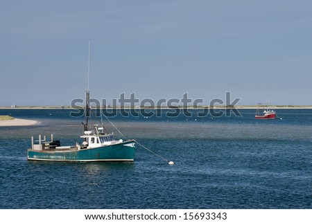 Old green and red fishing trawling boats anchored in calm blue water