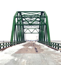 Old green bridge on a country road in Iowa with snow and grey sky