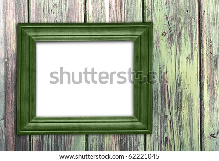 Old green frame on old wooden wall.