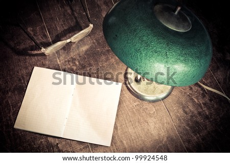Old green lamp, glasses and blank paper