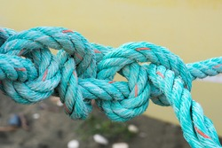 Old green rope knotted on a yellow background. Knot. Insoluble problem concept