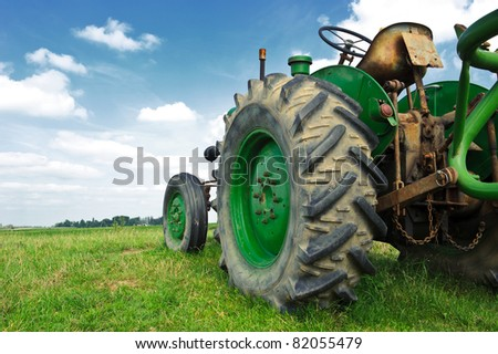 Old green tractor in the field with a cloudy sky