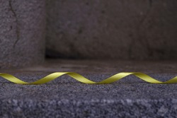 Old grey concrete structured cracked wall surface with granite pedestal and yellow waved ribbon. Dark abstract textured background with bright decorative detail and copy space.