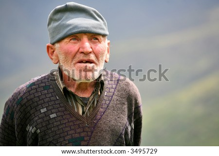 Old grey-haired man with mountains background
