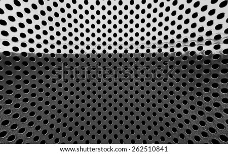 Old grey metal grille with a black hole.