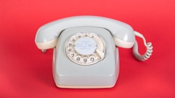 old grey telephone with dial plate, red background, German words for fire and emergency call on the dial plate