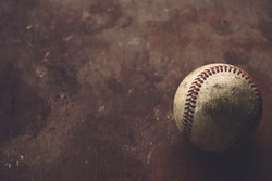 Old grunge baseball ball on brown texture background with copy space, blurred backdrop with shallow depth of field.