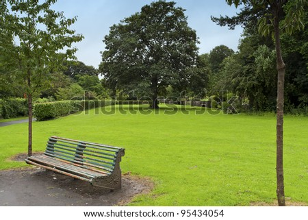 Old grunge bench in a peaceful green park