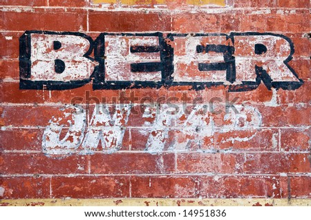 "Old grunge brick wall with inscription ""BEER ON TAP"""