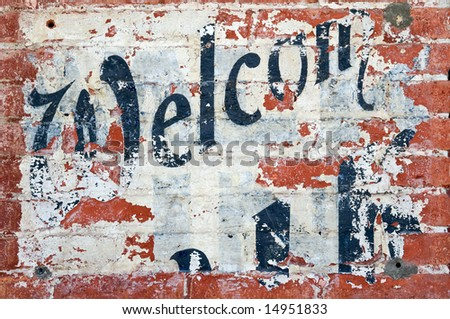 "Old grunge brick wall with inscription ""Welcome"""