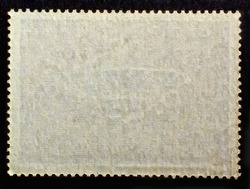 Old grunge posted stamp reverse  side with the edge of the sheet. Texture of paper..