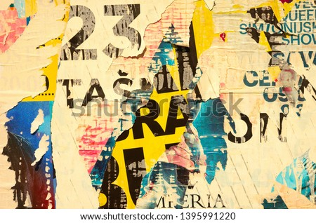 Old grunge ripped torn vintage collage colorful street posters creased crumpled paper surface backdrop