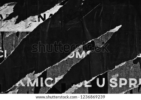 Old grunge ripped torn vintage collage street posters creased crumpled paper surface placard texture background backdrop dark black