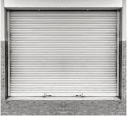 Old grunge weathered and dirty steel metal roller shutter door.