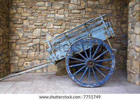 Old grunge wheelbarrow against stone wall background