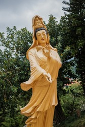 Old Guanyin, Traditional Chinese Goddess Golden Statue in temple, outdoor, daytime