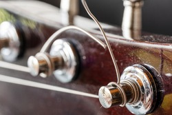 Old guitar keys. Musical equipment macro photo. Metal strings Acoustic guitar.