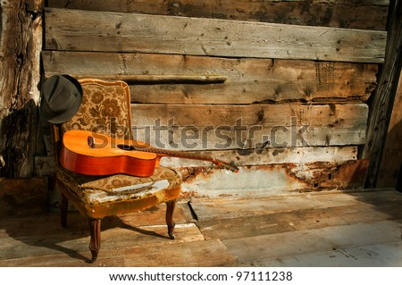 old guitar on a old chair with hat and wooden background