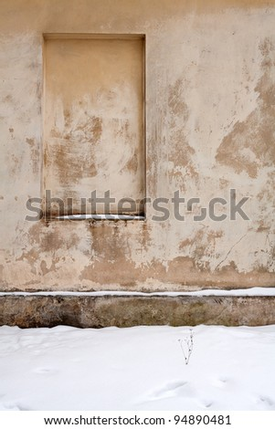 Old gungy wall with immured window in winter