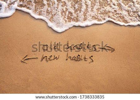 old habits vs new habits, life change concept written on sand Stockfoto ©