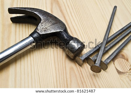 Old hammer and nails on wood background